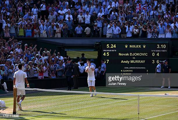 Andy Murray of Great Britain celebrates victory as he walks towards Novak Djokovic of Serbia after their Gentlemen's Singles Final match on day...