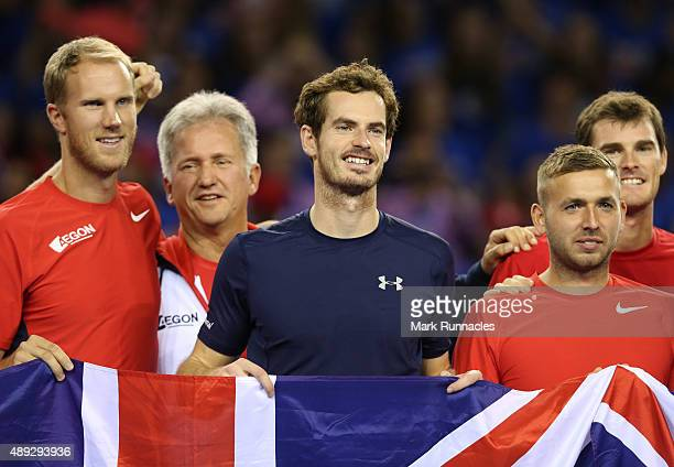 Andy Murray of Great Britain celebrates winning his singles match against Bernard Tomic of Australia with his fellow GB team mates taking Great...