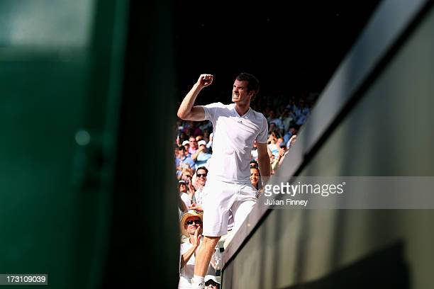 Andy Murray of Great Britain climbs up to his player's box to celebrate with friends family and members of his coaching team following his victory in...