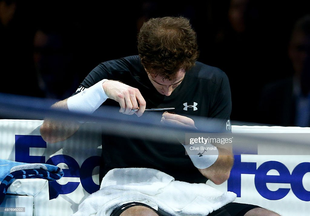 Andy Murray of Great Britain cuts his hair in-between games in his men's singles match against Rafael Nadal of Spain during day four of the Barclays ATP World Tour Finals at the O2 Arena on November 18, 2015 in London, England.