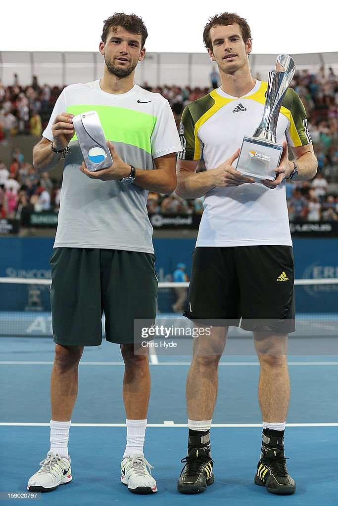 Andy Murray of Great Britain holds the winners trophy while his opponent Grigor Dimitrov of Bulgaria holds the runner up trophy after the finals match on day eight of the Brisbane International at Pat Rafter Arena on January 6, 2013 in Brisbane, Australia.