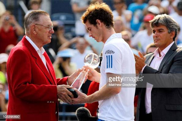 Andy Murray of Great Britain is presented the Rogers Cup trophy by an executive from Rogers after defeating Roger Federer of Switzerland during the...