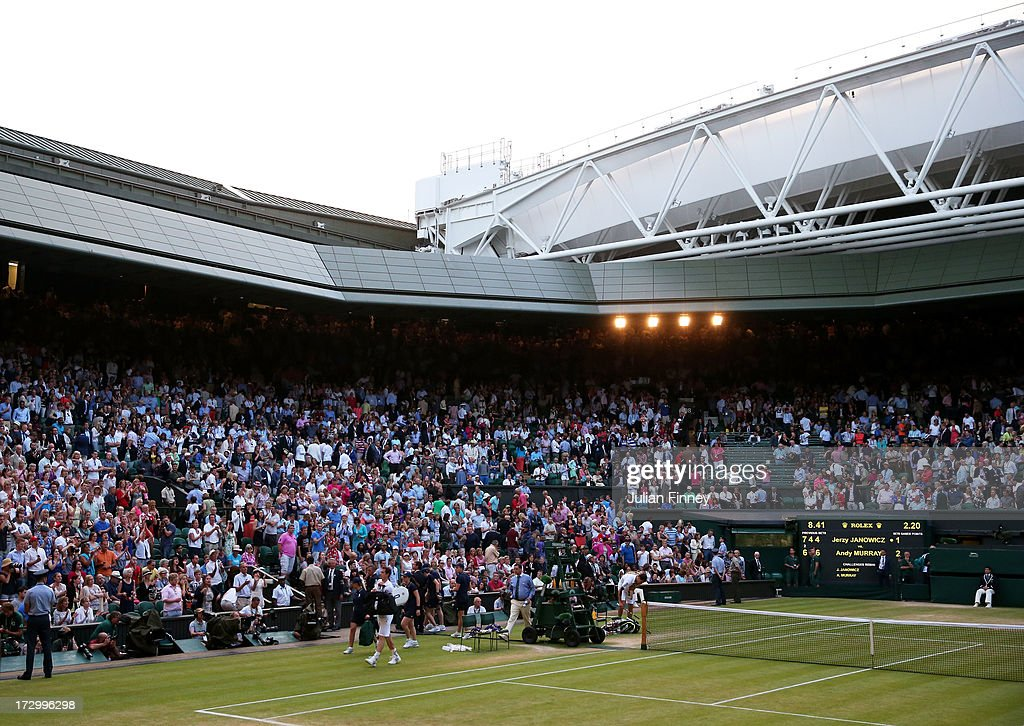 Andy Murray of Great Britain Jerzy Janowicz of Poland and Chair Umpire Jake Garner walk off Centre Court after Championships' referee Andrew Jarrett...