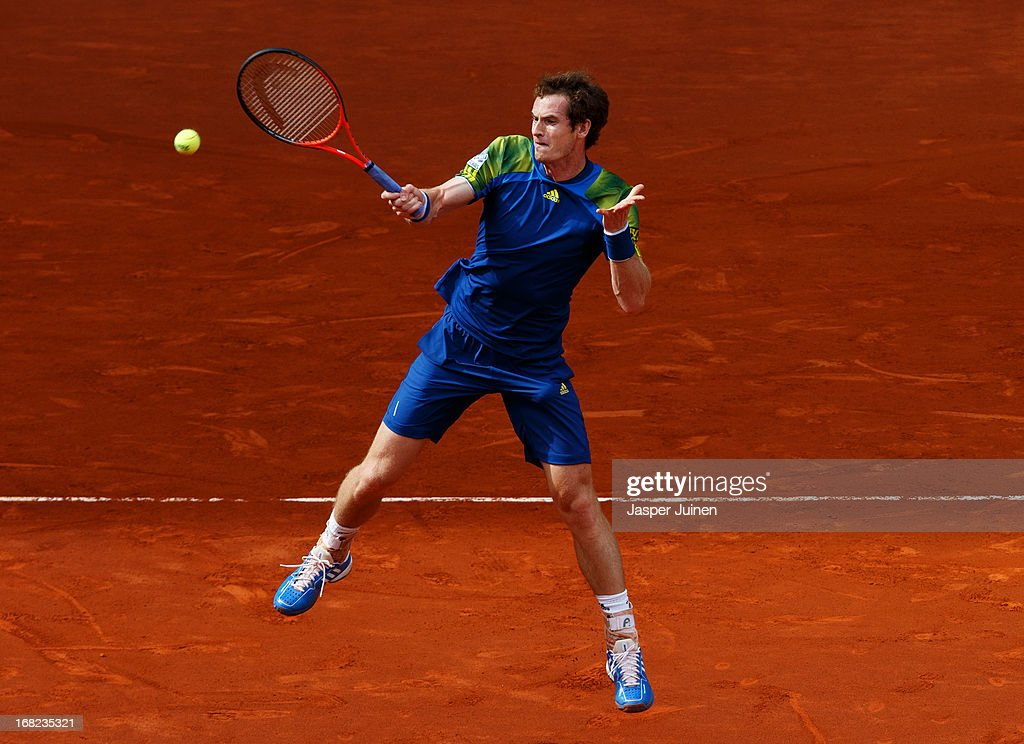 <a gi-track='captionPersonalityLinkClicked' href=/galleries/search?phrase=Andy+Murray+-+Tennis+Player&family=editorial&specificpeople=200668 ng-click='$event.stopPropagation()'>Andy Murray</a> of Great Britain jumps to play a backhand to Florian Mayer of Germany during his match on day four of the Mutua Madrid Open tennis tournament at the Caja Magica on May 7, 2013 in Madrid, Spain.