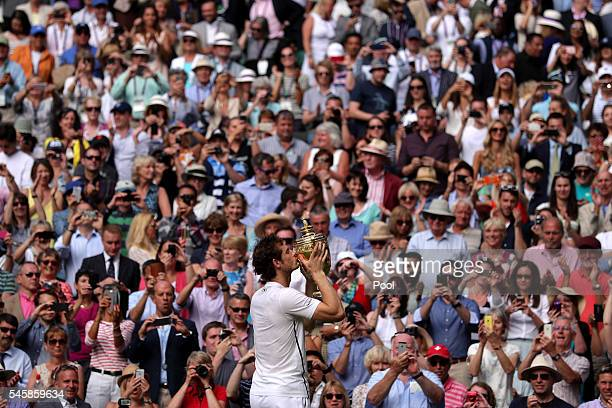 Andy Murray of Great Britain kisses the trophy following victory in the Men's Singles Final against Milos Raonic of Canada on day thirteen of the...