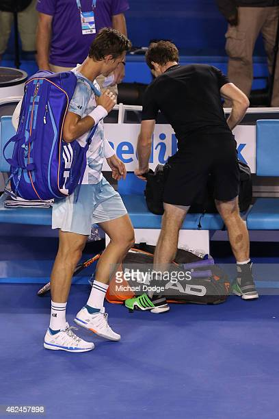 Andy Murray of Great Britain packs his bag as Tomas Berdych of the Czech Republic leaves the court after Murray won their semifinal match during day...