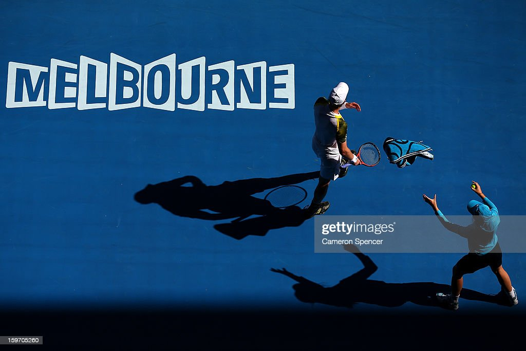 Andy Murray of Great Britain passes a towel to a ballboy in his third round match against Ricardas Berankis of Lithuania during day six of the 2013 Australian Open at Melbourne Park on January 19, 2013 in Melbourne, Australia.