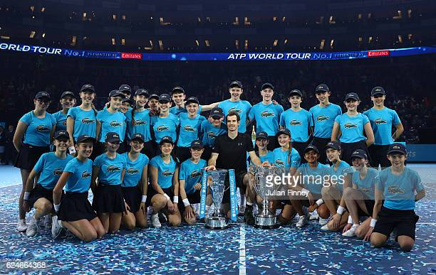 Andy Murray of Great Britain poses with the trophies and ball kids following his victory during the Singles Final against Novak Djokovic of Serbia at...