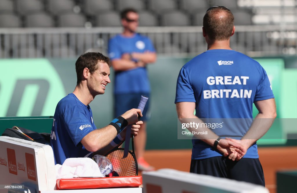Andy Murray of Great Britain puts a new grip on his racket watched by fitness trainer Matt Little during a practice session watched prior to the Davis Cup World Group first round between the U.S. and Great Britain at PETCO Park on January 29, 2014 in San Diego, California.
