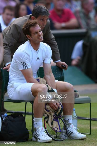 Andy Murray of Great Britain reacts as Championships' referee Andrew Jarrett explains the decision to close the roof during the Gentlemen's Singles...