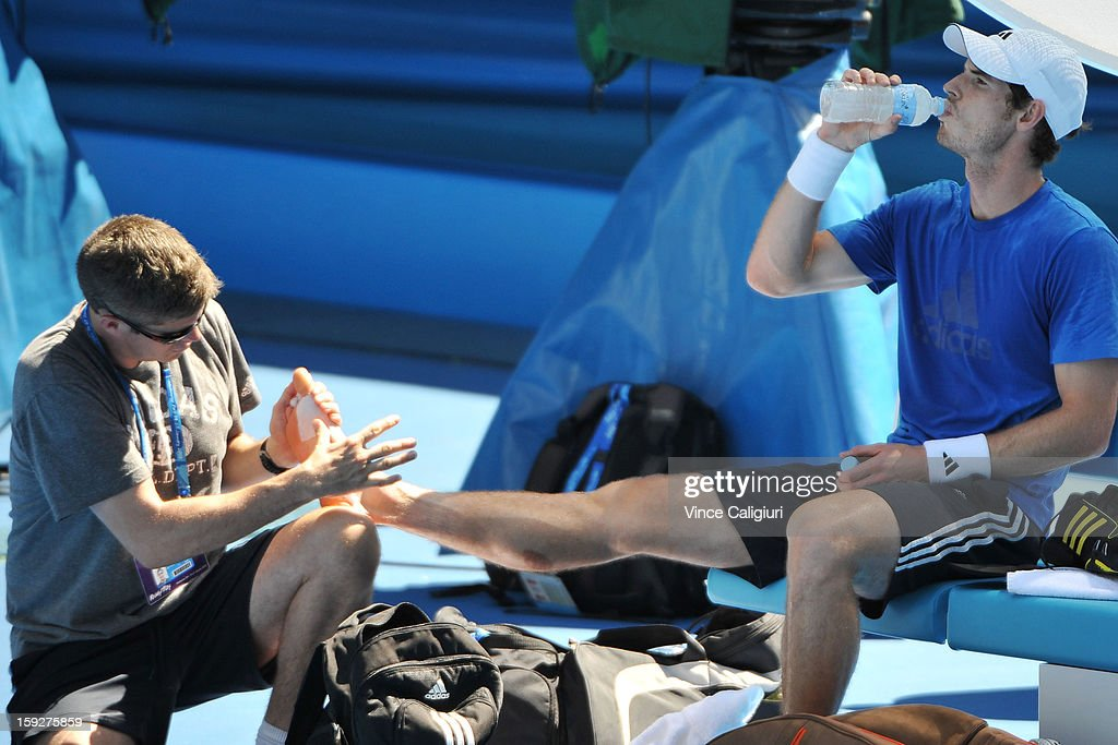 Andy Murray of Great Britain receives treatment on his foot from Andy Ireland during a practice session ahead of the 2013 Australian Open at Melbourne Park on January 11, 2013 in Melbourne, Australia.