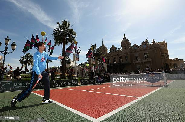 Andy Murray of Great Britain returns a ball to Novak Djokovic of Serbia as they play tennis in Casino Square prior to the ATP Monte Carlo Masters at...
