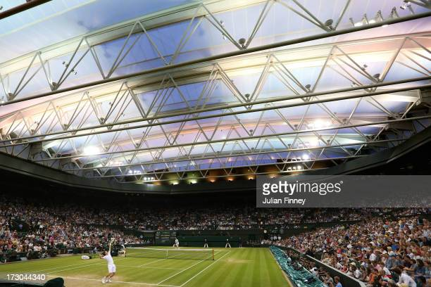 Andy Murray of Great Britain serves under a closed roof on Centre Court during the Gentlemen's Singles semifinal match against Jerzy Janowicz of...