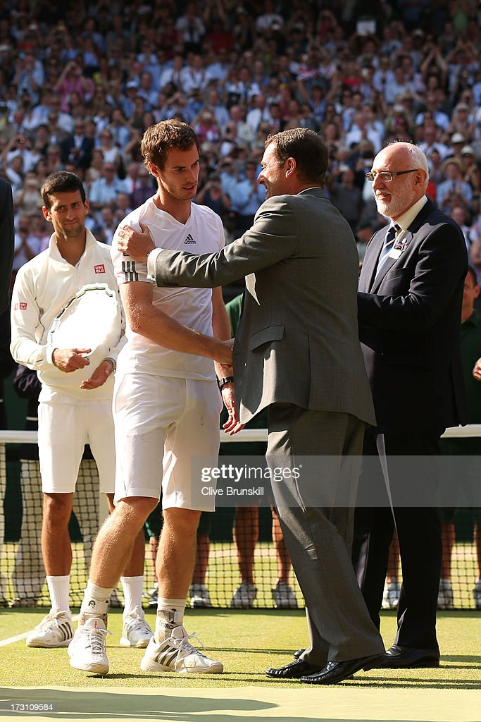 Andy Murray of Great Britain shakes hands with AELTC Chairman Philip Brook before receiving the Gentlemen's Singles Trophy on Centre Court following his victory in the Gentlemen's Singles Final match against Novak Djokovic of Serbia on day thirteen of the Wimbledon Lawn Tennis Championships at the All England Lawn Tennis and Croquet Club on July 7, 2013 in London, England.