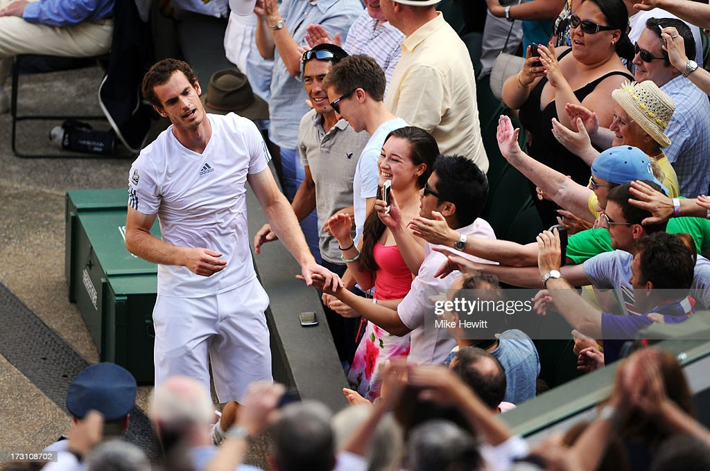 Andy Murray of Great Britain shakes hands with fans as he makes his way up to his player's box following his victory in the Gentlemen's Singles Final match against Novak Djokovic of Serbia on day thirteen of the Wimbledon Lawn Tennis Championships at the All England Lawn Tennis and Croquet Club on July 7, 2013 in London, England.