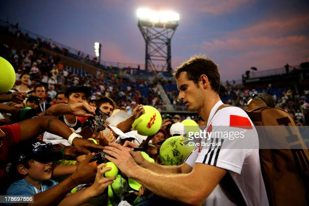 Andy Murray of Great Britain signs autographs for fans after his victory during his men's singles second round match against Leonardo Mayer of...