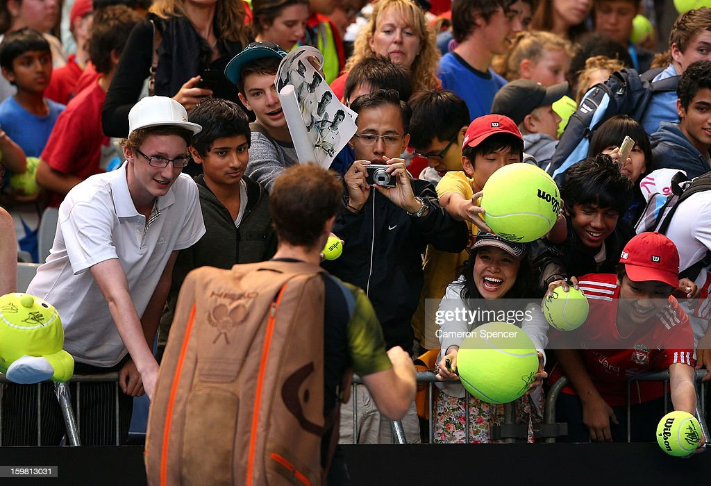 Andy Murray of Great Britain signs autographs for fans after winning his fourth round match against Gilles Simon of France during day eight of the 2013 Australian Open at Melbourne Park on January 21, 2013 in Melbourne, Australia.