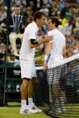 Andy Murray of Great Britain speaks with Jerzy Janowicz of Poland at the net after their Gentlemen's Singles semifinal match on day eleven of the...