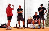Andy Murray of Great Britain takes a break at a practice session with coach Ivan Lendl and trainer Jez Green prior to his second round match during...