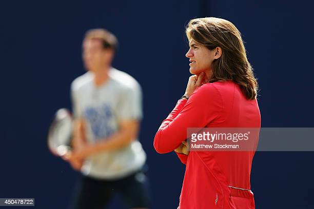 Andy Murray of Great Britain warms up on the practice courts watched by his new coach Amelie Mauresmo on day four of the Aegon Championships at...