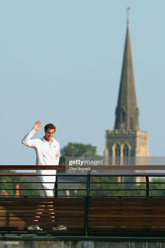 Andy Murray of Great Britain waves to the crowd backdropped by the Wimbledon Village Church following his victory in the Gentlemen's Singles Final match against Novak Djokovic of Serbia on day thirteen of the Wimbledon Lawn Tennis Championships at the All England Lawn Tennis and Croquet Club on July 7, 2013 in London, England.