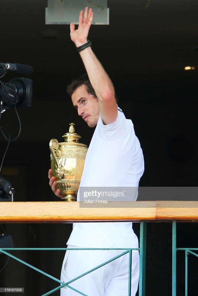 Andy Murray of Great Britain waves to the crowd from the Centre court balcony as he holds the Gentlemen's Singles Trophy following his victory in the Gentlemen's Singles Final match against Novak Djokovic of Serbia on day thirteen of the Wimbledon Lawn Tennis Championships at the All England Lawn Tennis and Croquet Club on July 7, 2013 in London, England.