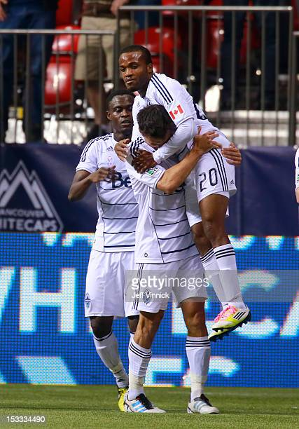 Andy O'Brien of the Vancouver Whitecaps FC hoists goal scorer Dane Richards in front of Gershon Koffie against Chivas USA during their MLS game...