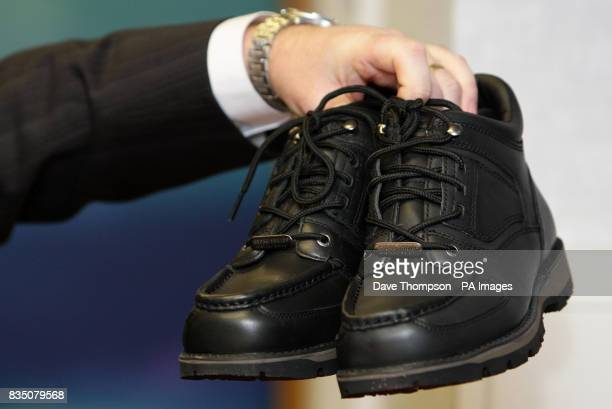 DI Andy O'Connor holds up a pair of Rockport shoes similar to that worn by Gary Finlay who Merseyside Police wish to question in relation to the...
