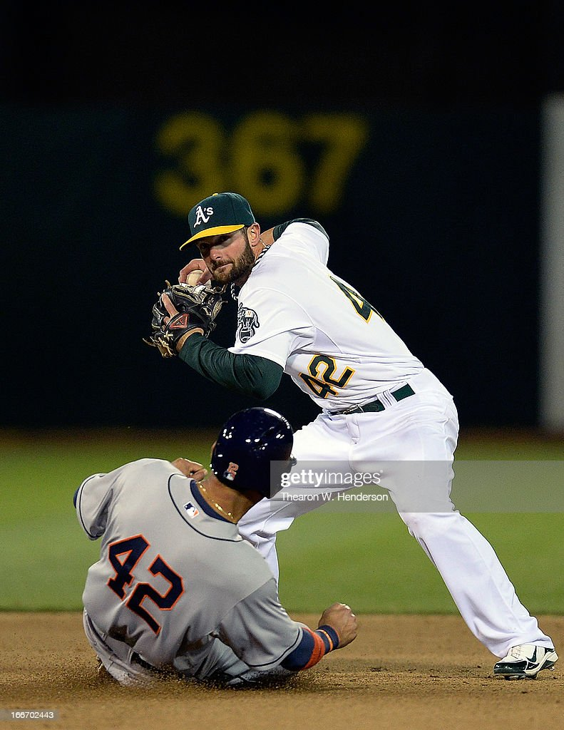 Andy Parrino of the Oakland Athletics gets the force out at second base on Carlos Pena of the Houston Astros in the seventh inning at O.co Coliseum on April 15, 2013 in Oakland, California. All uniformed team members are wearing jersey number 42 in honor of Jackie Robinson Day.