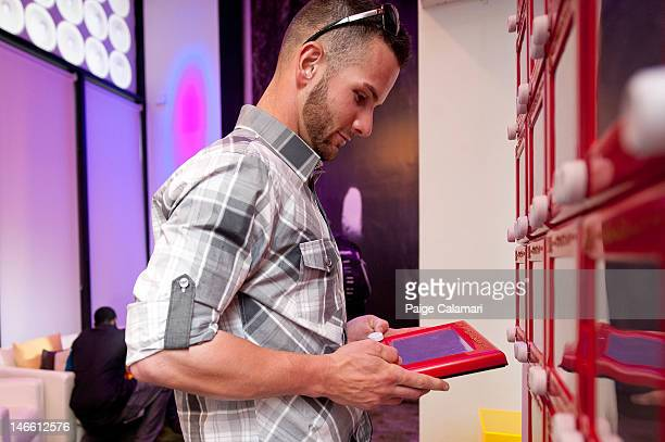 Andy Parrino of the San Diego Padres plays with an EtchaSketch at the MLB Fan Cave Friday May 25 at Broadway and 4th Street in New York City