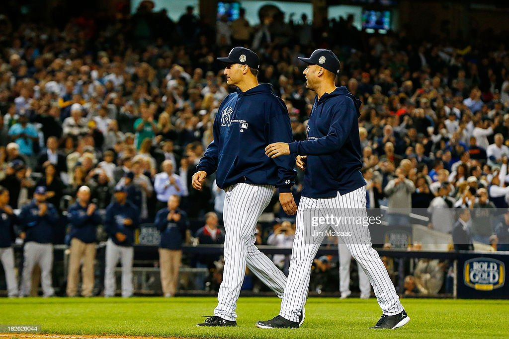 Andy Pettitte #46 (L) and Derek Jeter #2 of the New York Yankees walk back to the dugout after removing teammate Mariano Rivera from a game against the Tampa Bay Rays in the ninth inning at Yankee Stadium on September 26, 2013 in the Bronx borough of New York City. The Rays defeated the Yankees 4-0.