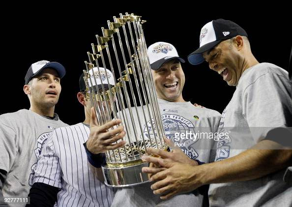 Andy Pettitte Jorge Posada Derek Jeter and Mariano Rivera of the New York Yankees celebrate with the trophy after their 73 win against the...