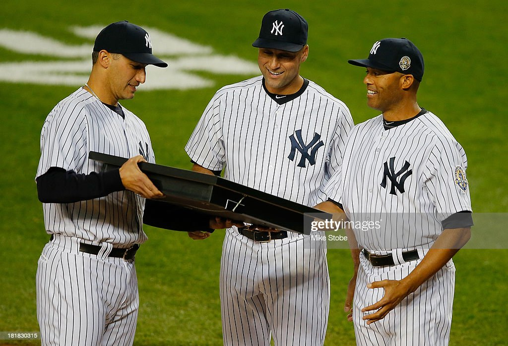 <a gi-track='captionPersonalityLinkClicked' href=/galleries/search?phrase=Andy+Pettitte&family=editorial&specificpeople=201753 ng-click='$event.stopPropagation()'>Andy Pettitte</a> #46 of the New York Yankees is joined by <a gi-track='captionPersonalityLinkClicked' href=/galleries/search?phrase=Derek+Jeter&family=editorial&specificpeople=167125 ng-click='$event.stopPropagation()'>Derek Jeter</a> #2 and <a gi-track='captionPersonalityLinkClicked' href=/galleries/search?phrase=Mariano+Rivera&family=editorial&specificpeople=201607 ng-click='$event.stopPropagation()'>Mariano Rivera</a> #42 to honor Pettitte, who is retiring from the Yankees, before their game against the Tampa Bay Rays at Yankee Stadium on September 25, 2013 in the Bronx borough of New York City. Rays defeated the Yankees 8-3.