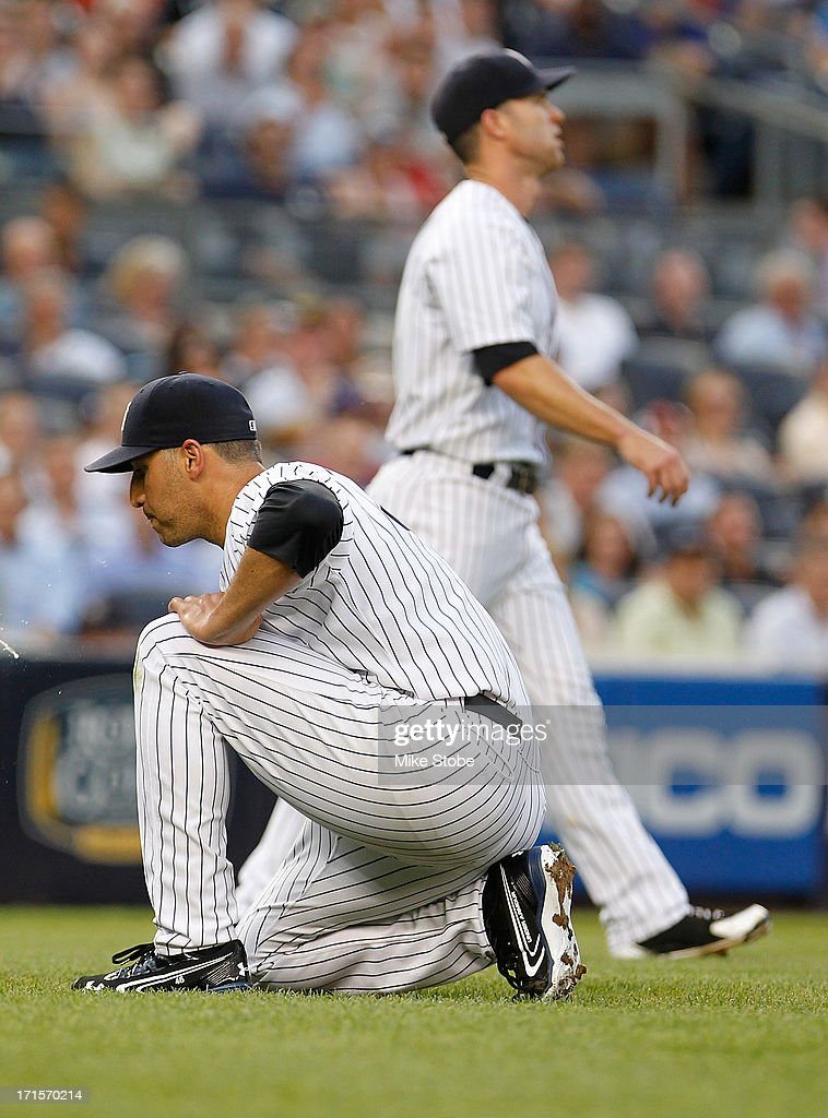 Andy Pettitte #46 of the New York Yankees reacts after Jayson Nix #17 makes a throwing error on Elvis Andrus #1 of the Texas Rangers bunt attempt in the third inning at Yankee Stadium on June 26, 2013 in the Bronx borough of New York City.