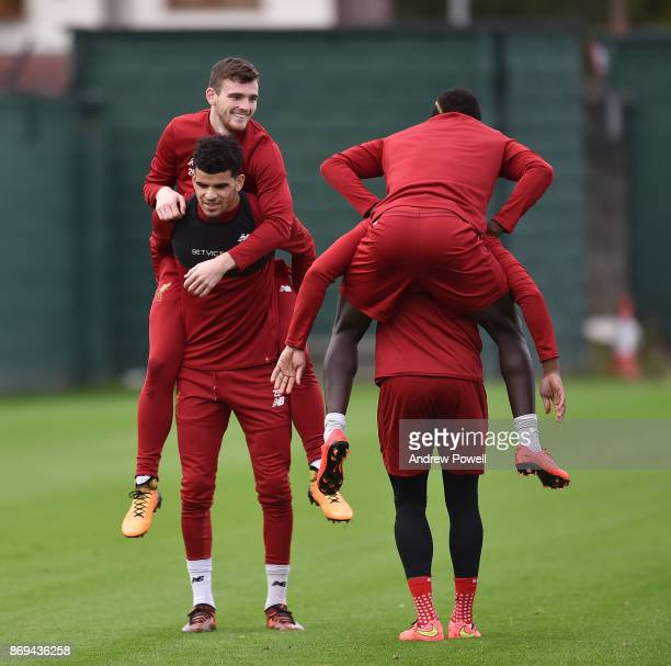 Andy Robertson rides the back of Dominic Solanke while Sadio Mane rides the back of Daniel Sturridge of Liverpool during a training session at...