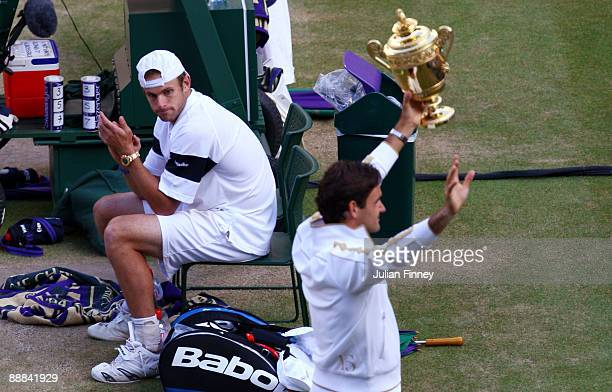 Andy Roddick of USA looks despondent as Roger Federer of Switzerland celebrates with the trophy during the men's singles final match on Day Thirteen...