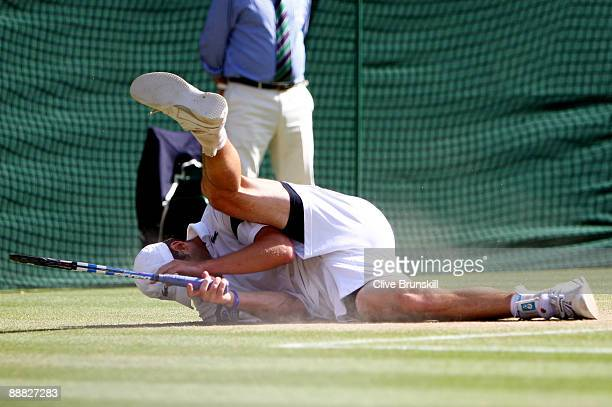 Andy Roddick of USA tumbles during the men's singles final match against Roger Federer of Switzerland on Day Thirteen of the Wimbledon Lawn Tennis...