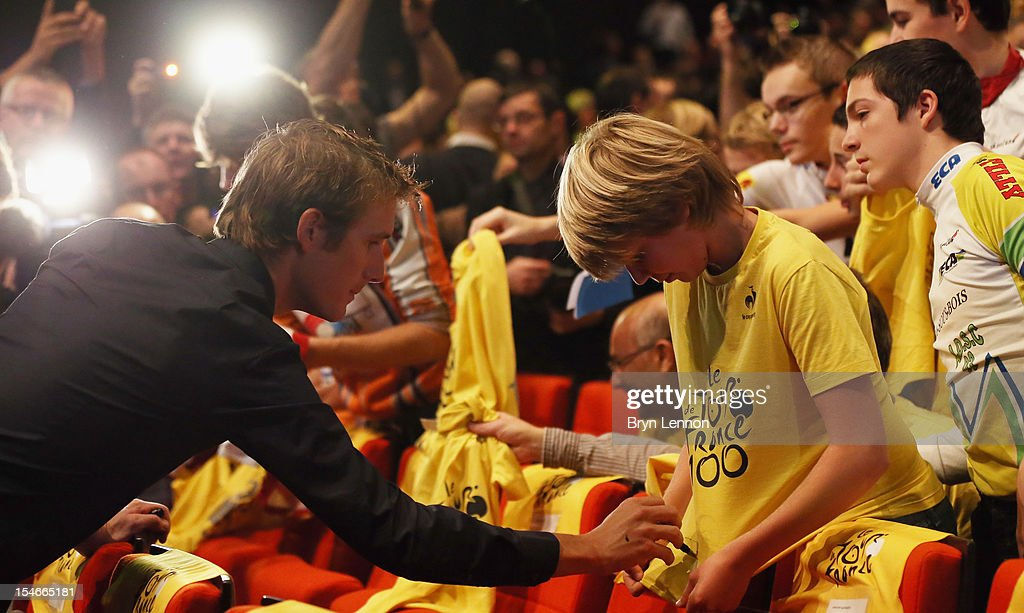 <a gi-track='captionPersonalityLinkClicked' href=/galleries/search?phrase=Andy+Schleck&family=editorial&specificpeople=768445 ng-click='$event.stopPropagation()'>Andy Schleck</a> of Luxembourg autographs a T-shirt during the 2013 Tour de France Route Presentation at the Palais des Congres de Paris on October 24, 2012 in Paris, France.