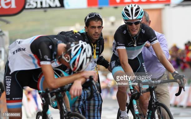Andy Schleck of Luxemburg and Team LeopardTrek crosses the finishing line alongside his exhausted brother Frank Schleck and claim the race leaders...