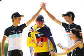 Andy Schleck of team Leopard congratulates his teammate and brother Frank Schleck as Cadel Evans of team BMC celebrates winning the 2011 Tour De...