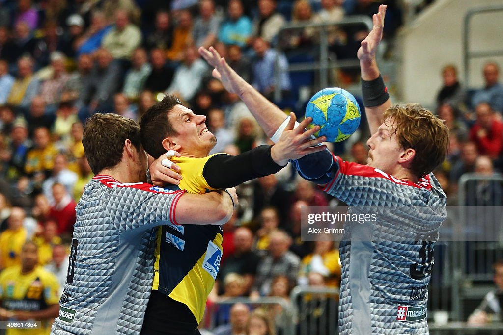 Andy Schmid (C) of Rhein-Neckar Loewen is challenged by <a gi-track='captionPersonalityLinkClicked' href=/galleries/search?phrase=Jakov+Gojun&family=editorial&specificpeople=5678289 ng-click='$event.stopPropagation()'>Jakov Gojun</a> (L) and Jesper Nielsen of Berlin during the DKB HBL Bundesliga match between Rhein-Neckar Loewen and Fuechse Berlin at SAP Arena on November 24, 2015 in Mannheim, Germany.