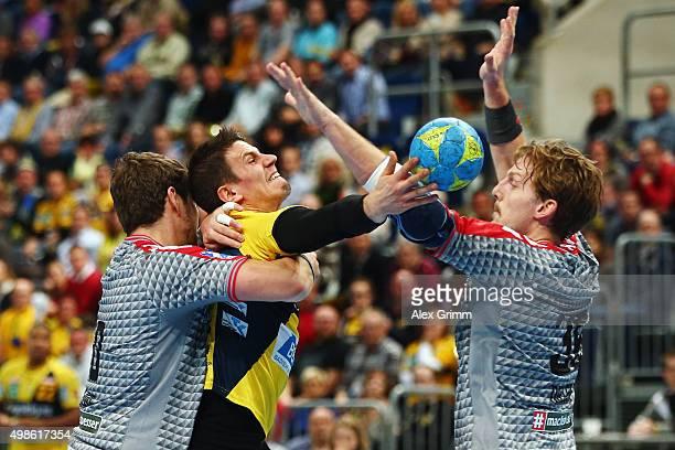 Andy Schmid of RheinNeckar Loewen is challenged by Jakov Gojun and Jesper Nielsen of Berlin during the DKB HBL Bundesliga match between RheinNeckar...