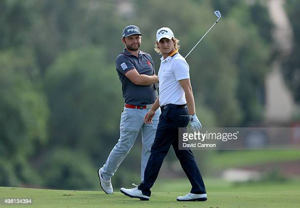 Andy Sullivan of England plays his second shot on the par 4 third hole as his playing partner Emiliano Grillo of Argentina walks past during the...