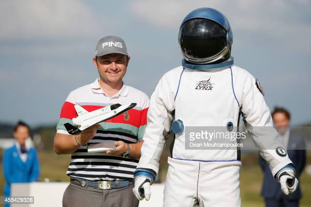 Andy Sullivan of England poses with his trophy and an astronaut from the XCOR space ship after the final round of the KLM Open held at De Kennemer...