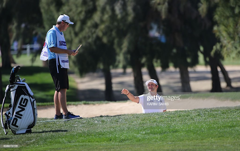 Andy Sullivan (R) of England talks to his caddy during the final round of the 2016 Dubai Desert Classic at the Emirates Golf Club in Dubai on February 7, 2016. SAHIB