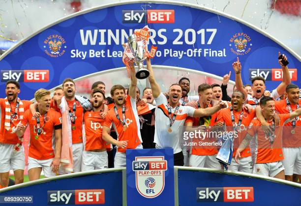Andy Taylor and Tom Aldred of Blackpool hold the trophy as they celebrate victory and promotion after the Sky Bet League Two Playoff Final between...