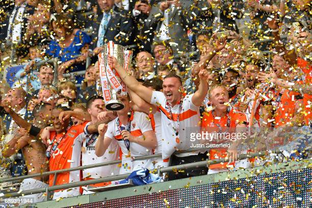 Andy Taylor and Tom Aldred of Blackpool lift the trophy as they celebrate victory and promotion with team mates after the Sky Bet League Two Playoff...