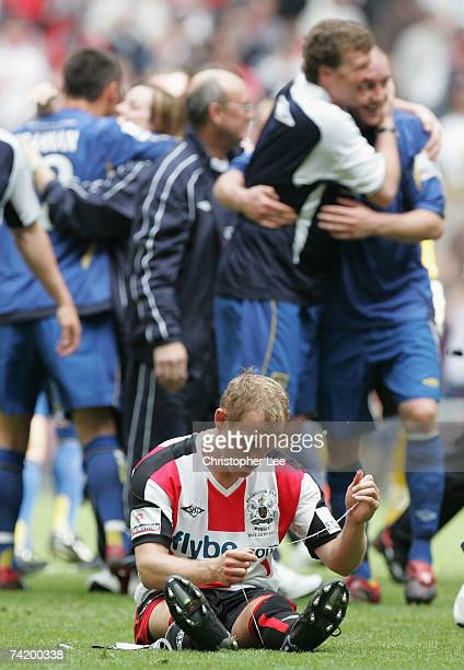 Andy Taylor of Exeter looks dejected as Morecambe celebrate during the Nationwide Conference Promotion Final between Exeter City and Morecambe at...