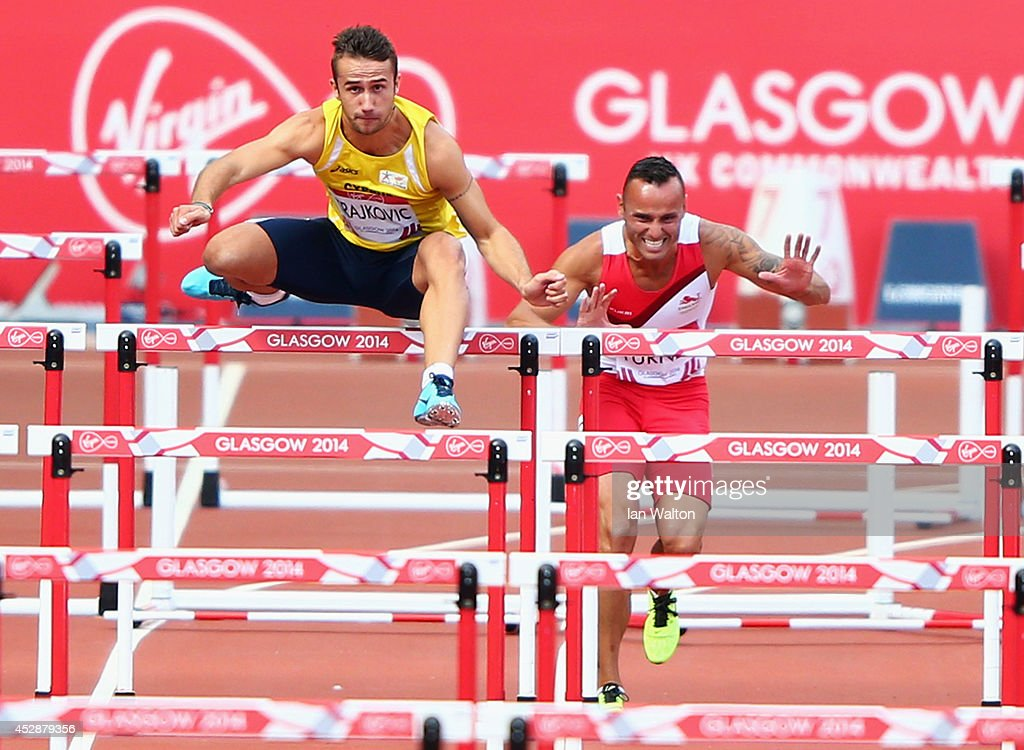 Andy Turner of England (R) hits the hurdle as he competes in Men's 110 metres hurdles Round 1 at Hampden Park during day six of the Glasgow 2014 Commonwealth Games on July 29, 2014 in Glasgow, United Kingdom.