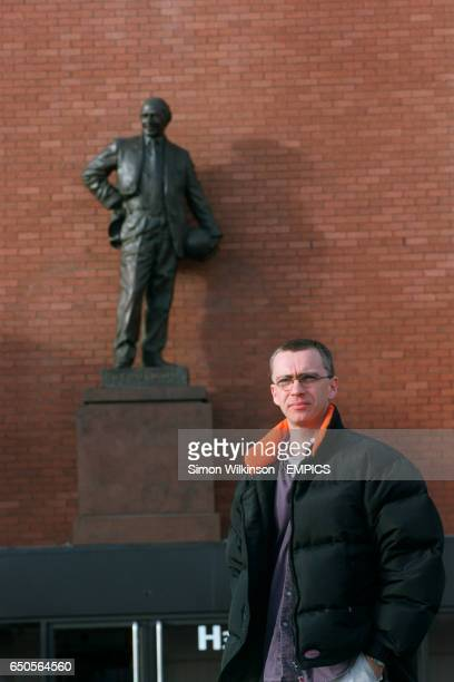 Andy Walsh chairman of the Independent Manchester United Supporters Association standing in front of a statue of Sir Matt Busby at Old Trafford home...